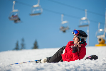 Smiling girl lying with skis on snowy at mountain top, looking to the sun and having fun at a winter resort, ski lifts and blue sky in background. Carpathian mountains