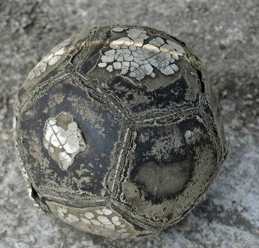 Worn football on concrete ground