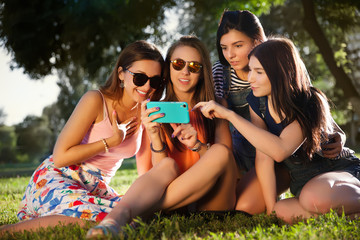 Summer outdoor portrait of three friends fun girls taking photos with a smartphone at bright sunset.