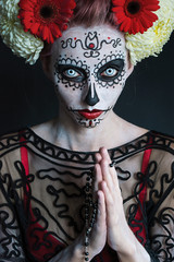 beautiful girl with a pattern on the face and red flowers in her hair Los Muertos