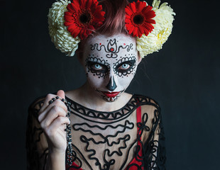 frightening photograph of a beautiful girl with a pattern on the face and red flowers in her hair Los Muertos