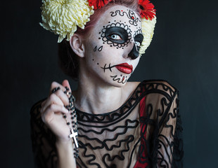 photo portrait of girl to dress up in the image of the goddess of death with the rosary in his hands praying Los Muertos