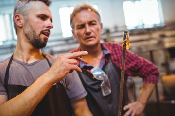 Glassblower interacting with each other in factory