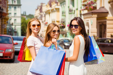 Attractive happy customers with packets of clothes after shoppin