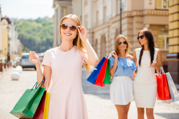 Cheerful happy woman with shopping bags spending time with frien