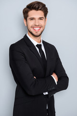 Successful businessman with beaming smile standing with crossed