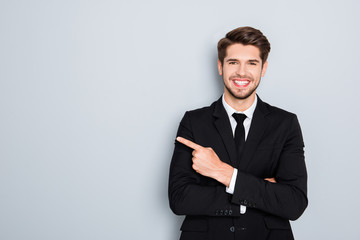 Young handsome businessman with beaming smile pointing with fing