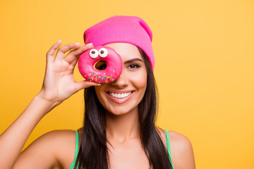 Funny girl  in pink hat with beaming smile holding donut near ey Fototapete