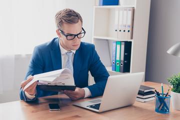 Portrait of smart businessman in glasses reading financial repor