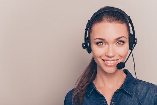 Beautiful consultant of call center in headphones on gray backgr
