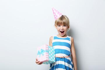 Portrait of  little girl in birthday cap on grey background