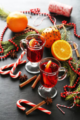 Mulled wine in glass on black wooden table