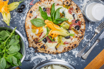 Traditional italian pizza with mozzarella, salami, ricotta and pumpkin flowers on chalkboard