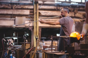 Glassblower shaping glass on blowpipe in factory