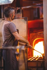 Glassblower heating a glass in furnace