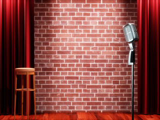 Vintage metal microphone against red curtain on empty theatre stage