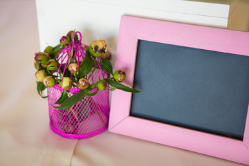 Blank photo frame and flowers bouquet. Over wooden table