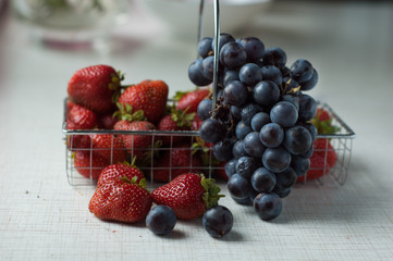 Strawberries and grapes in a small basket on a metal table.