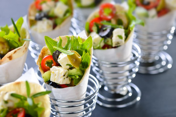 Mini-Wraps gefüllt mit griechischem Bauernsalat mit Feta und Oliven - Mini tortillas stuffed with Greek farmers salad with feta cheese and olives, served in wire egg cups