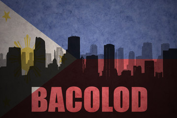 abstract silhouette of the city with text Bacolod at the vintage philippines flag background