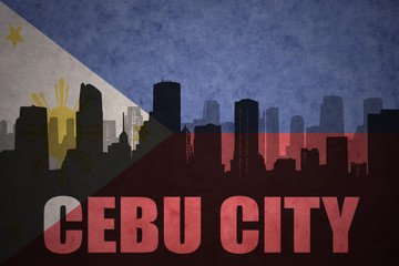 abstract silhouette of the city with text Cebu City at the vintage philippines flag background