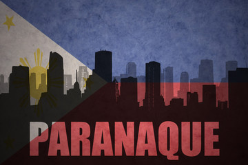 abstract silhouette of the city with text Paranaque at the vintage philippines flag background
