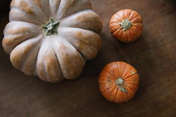 three pumpkins on the wooden table