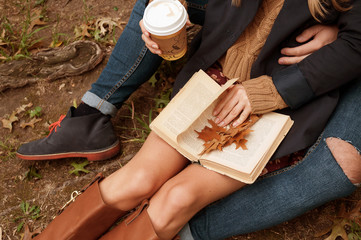 Romantic couple drinking coffee relaxing in the park in autumn