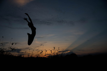 Silhouette woman jumping at sunset