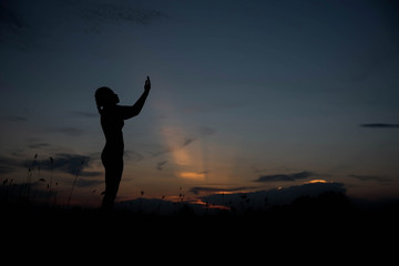 silhouette young woman alone with God at sunset