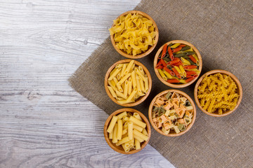 Various combinations of pasta on wooden background, burlap bags, bamboo bowls. diet and nutritional concept.