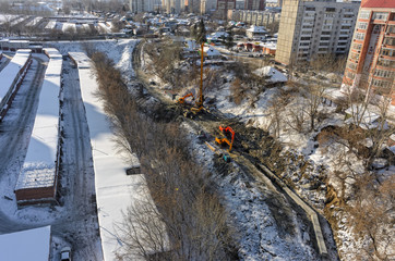 Tyumen, Russia - February 15, 2016: Aerial view onto construction works on strengthening of Tyumenka river bank near Polevaya Street