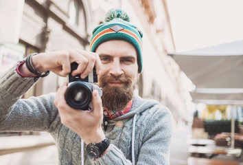 Young cheerful man photographer takes images with vintage camera
