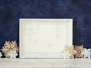 Christmas decoration and photo frame on the blue vintage background. Paper snowflakes and stars. New year greeting card template. Holiday mock up. Scandinavian style.