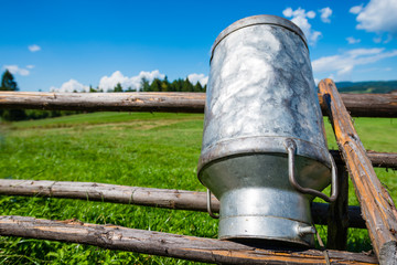 Old Milk Can Made of Aluminum. Old milk can made of metal to dry on a wooden stand - upside down - shallow depth of field