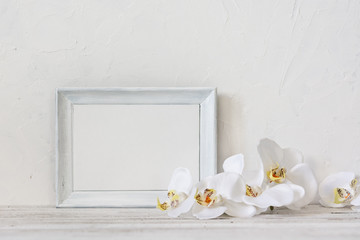 White photo frame with white orchids on the vintage table. Picture frame.