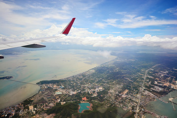 Wing of an airplane flying above the ocean, Hatyai Thailand