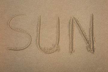 The Word Sun Written in the Sand on a Beach