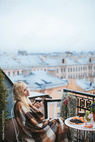 Woman with tea sheltered blanket breakfast on the balcony for Balcony overlooking city