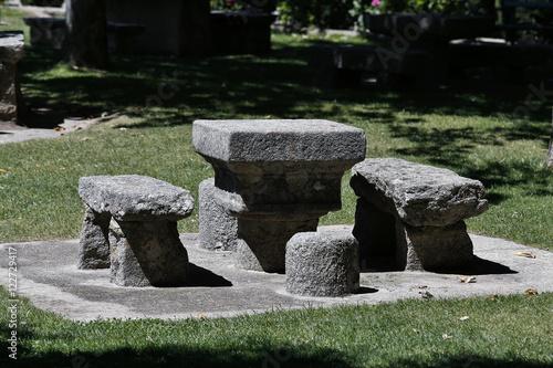 Mesa sillas y bancos de piedra en un jard n stock photo for Bancos de piedra para jardin