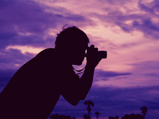 The Silhouette of the man who take a photo in the evening.