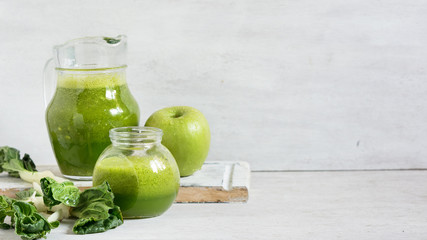 Green smoothie in jars and apple on the grey background.