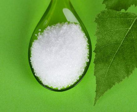 Xylitol birch sugar on plastic spoon with birch leaves on green background. White granulated sugar alcohol substitute used as sweetener that taste like table sugar, extracted from wood of birch trees.