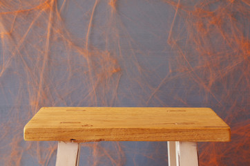 Empty rustic table in front of spider web background