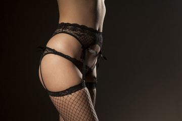 garter, sexy panties and fishnet stockings on dark background