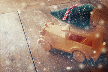 Wooden car carrying a christmas tree. Glitter overlay
