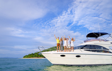 Friendship and vacation. Happy young people standing on the yacht deck and enjoying the view, sailing the sea.