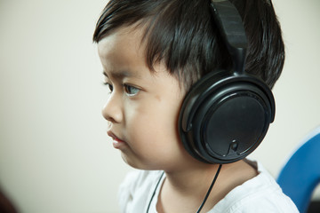 Happy cheerful boy with headphones listening to music on a gray