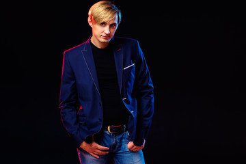 Fashion and confidence. Studio portrait of handsome young blonde man in jacket. Black background.