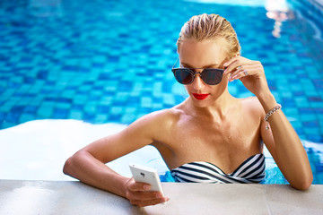 Vacation and technology. Pretty young woman using smartphone in swimming pool.